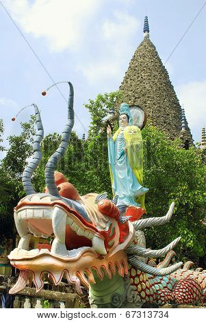 A sculpture of a mythical dragon head on the background statue of the goddess Guan Yin