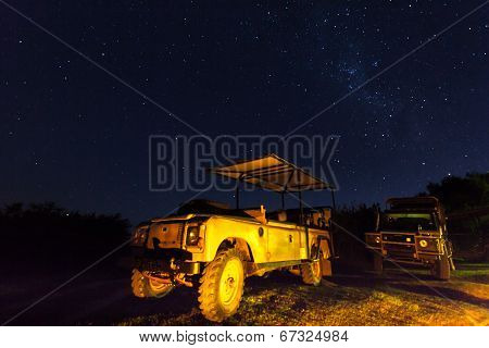 Landrovers with golden reflection under the stars