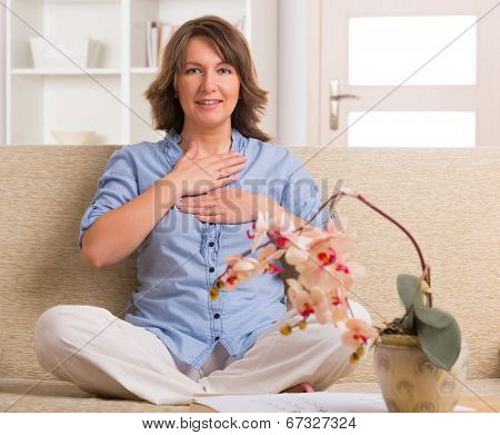 Woman practicing self Reiki transfering energy through palms, a kind of energy medicine. poster