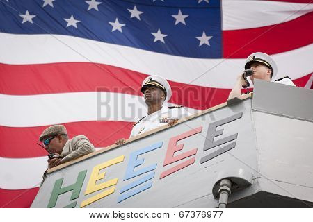 STATEN ISLAND, NY - MAY 21, 2014: The American Flag flies behind the harbor master, commander, and conning officer on the USS McFaul (DDG 074) as they manuever into port at Sullivans Piers for Fleet Week.