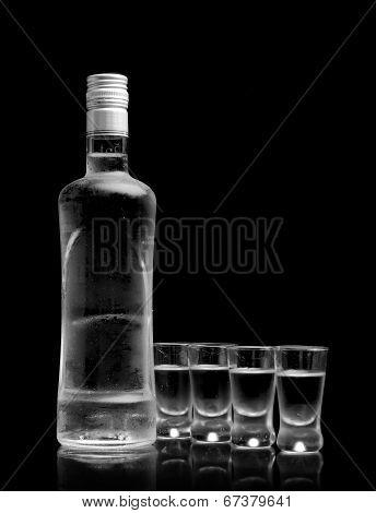 Bottle With Many Glasses Of Vodka Isolated On Black Background