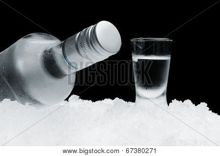Bottle With Glass Of Vodka Lying On Ice On Black Background