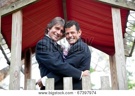 Newly married gay couple embracing under an outdoor canopy.