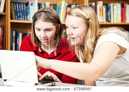 Teen girls using a computer in the library.