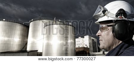 refinery worker with giant fuel storage tanks at sunset