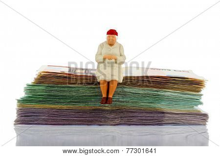 figure of an old woman sitting on a stack of bills, symbolic photo for pension and retirement