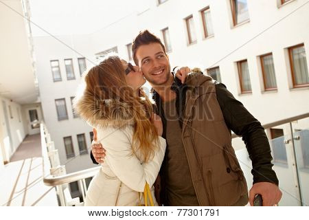Happy young couple kissing in apartment house, smiling, embracing.