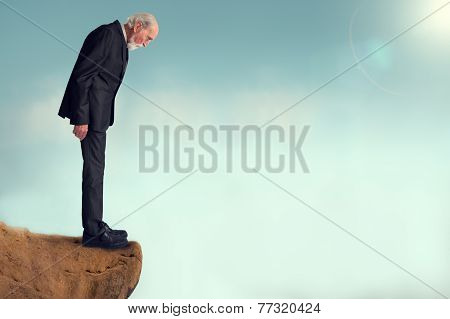 Senior Man Looking Down From A Cliff