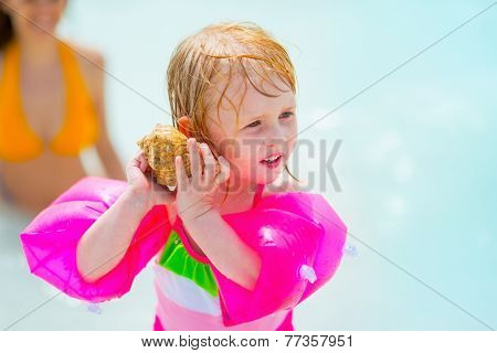 Baby girl in inflatable armband listening sound of sea in shell poster