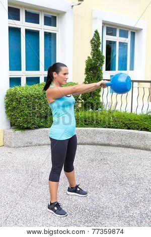 Beautiful sporty hispanic woman in blue training with kettlebell showing the swing routine