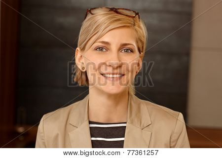 Closeup portrait of smiling young blonde woman looking at camera.