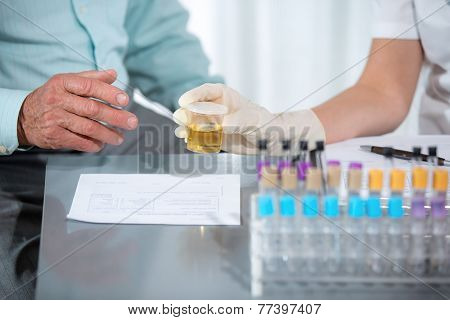 Doctor passes urine cups to patients