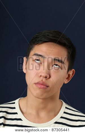 Funny young Asian man making face and rolling eyes up