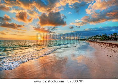 Bright and dynamic sea beach sunrise with bright blue skies and colorful clouds