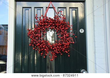 Berry Christmas Wreath With Decorations On A Door
