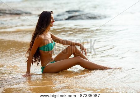 tanned brunette sitting on the beach