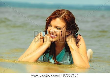 Vacation. Sensual girl wet cloth in water on the coast. Redhair woman having fun relaxing on the sea. Summertime. poster