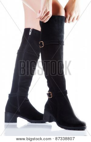 Beautiful female legs in black suede boots on a white background. hand tighten the boots