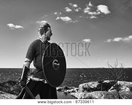 Medieval viking warrior wearing chainmail he has the sword and the shield north nature on background black and white image poster