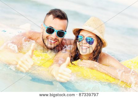A picture of a young couple swimming on a matress in the sea