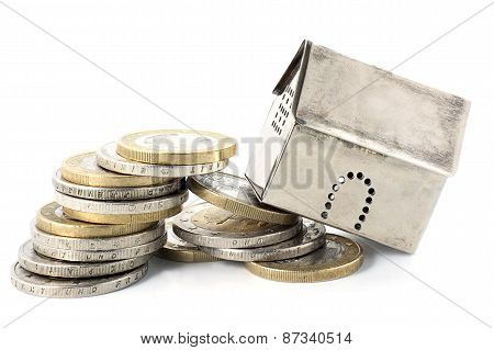 Property Finance Collapses, House Model Falls From Overturning Pile Of Coins  Isolated On White