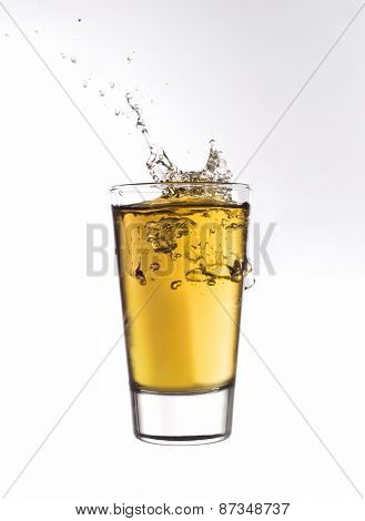 Splash in a glass of orange lemonade isolated on white background