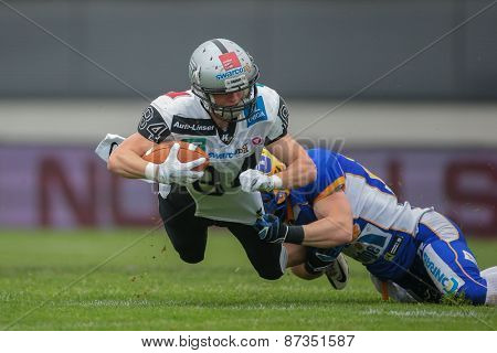 GRAZ, AUSTRIA - APRIL 26, 2014: WR Clemens Erlsbacher (#84 Raiders) is tackled by DB Johannes Winter (#25 Giants).