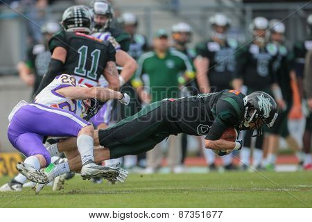 VIENNA, AUSTRIA - APRIL 13, 2014: WR Johannes Prammer (#88 Dragons) is tackled by DB Andreas Lunzer (#29 Vikings).