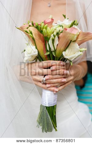 Beautiful wedding bouquet of rose Vendella, calla and freesia flowers in hands of the bride