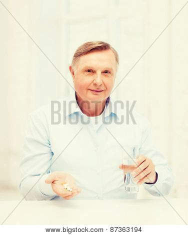 healthcare, madicine, pharmacy and elderly concept - old man with pills and glass of water