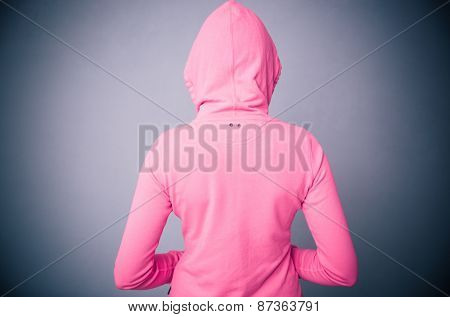 Back view protrait of a woman in pink jacket with hood over gray background