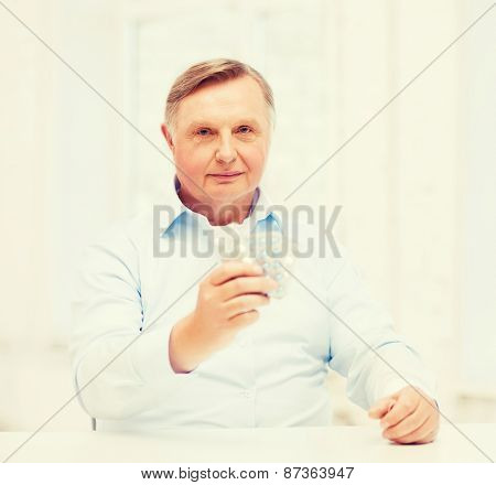 healthcare, madicine, pharmacy and elderly concept - old man with pack of pills
