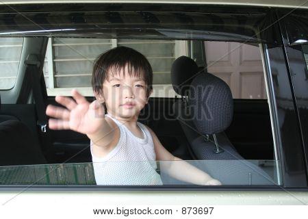 Boy Waving In The Car