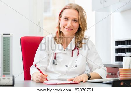 Young gynaecologist writing medical prescription in surgery at desk