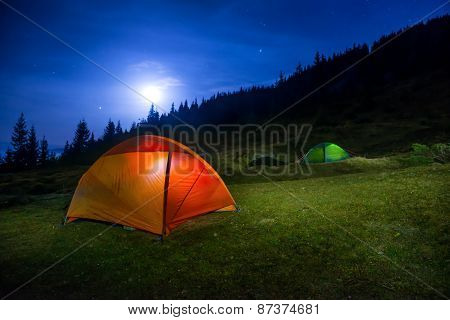 Two Illuminated Orange And Green Camping Tents