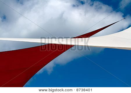 Red and White Canvas sails against bright blue sky