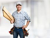 Portrait of a smiling carpenter holding wood planks. Bright background poster