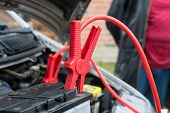 car battery clamped with red jumper cable to recharge the power poster