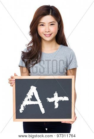Young woman with chalkboard showing mark A plus