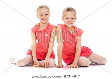 Two sisters sit on the floor