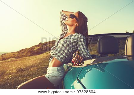 Attractive Young Woman Posing Leaning On Convertible Car At Sunset