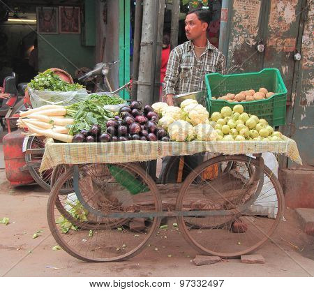 man sells vegetables in the market of Delhi, India