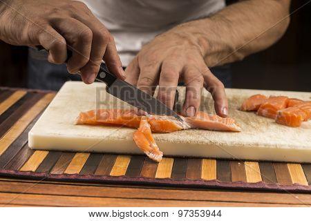 fishmonger prepares a salmon fillet