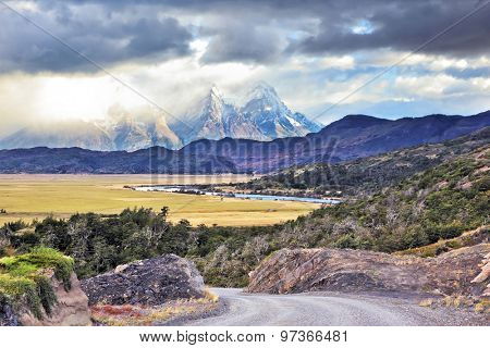 The road between turned yellow hills and river goes to snow-covered black rocks. Patagonia. Vertiginous landscape in the Chilean Andes