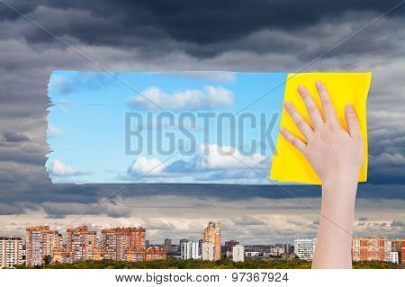 Hand Deletes Dark Clouds Over City By Yellow Cloth