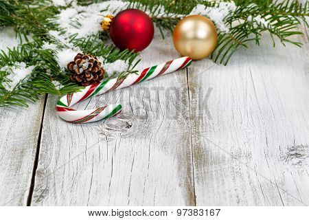 Candy Cane With Snow Covered Fir Branches And Ornaments On Rustic White Wooden Boards