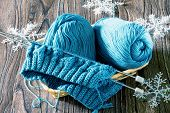 Wool yarn and needles. Needlework accessories on wooden background. poster