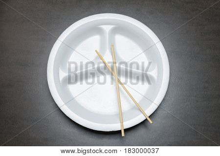 Empty disposable plastic plate on black table. White plate with three sections for food with bamboo chopsticks