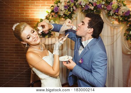 Newlyweds Feed Each Other With A Wedding Cake