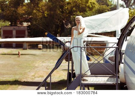 Beautiful bride in the windy weather near the airplane